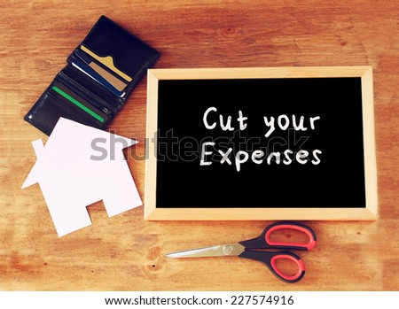 "top view of blackboard with the slogan ""cut your expenses"" scissors, wallet with credit cards and house shaped paper. household or family expenses concept - stock photo"