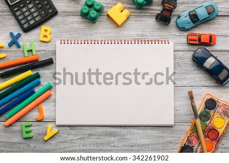 Top view of blank notebook, school supplies and toys on a white wooden desk. - stock photo