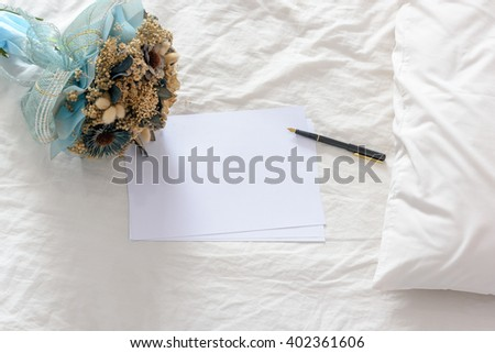Top view of blank papers with a fountain pen decorated with a bouquet of dried flowers on an unmade / untidy bed with a white pillow. Space for leaving messages / notes to someone in special occasions - stock photo
