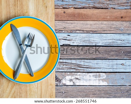Top view of blank plate on table top with rustic wooden copy space background - stock photo