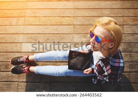 Top view of blonde hair woman in summer colorful glasses using digital tablet while sitting on a wooden pier, female tourist holding tablet while sitting outdoors at sunny day, girl browsing outside - stock photo