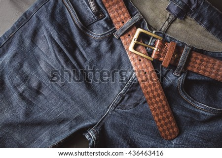 Top view of blue jeans with leather belt - stock photo