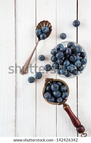 Top view of blueberries or bilberries in an antique tea strainer, glass bowl and old spoon over a white wooden table - stock photo
