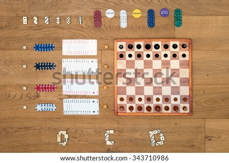 Top view of Board game items and gambling objects, such as a chess board and pieces, cards, chips, and dominoes neatly aligned on a wooden surface, seen from above - stock photo