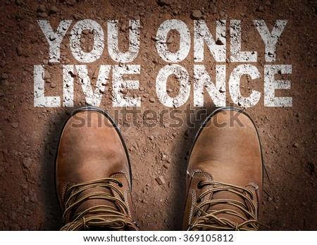 Top View of Boot on the trail with the text: You Only Live Once - stock photo