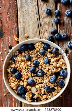 Top view of bowl with granola and fresh blueberries over rustic wooden background.  - stock photo