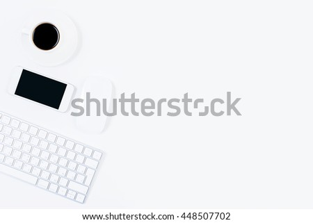 Top view of bright office desktop with blank mobile phone, computer mouse, keyboard and coffee cup. Mock up