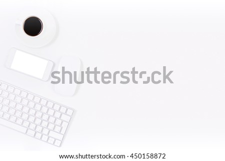 Top view of bright office desktop with blank white mobile phone, computer mouse, keyboard and coffee cup. Mock up