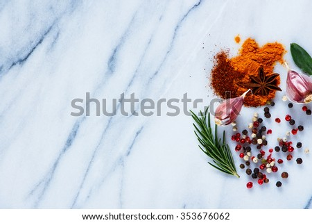 Top view of bright spices (curry, paprika, garlic, rosemary, pepper) on marble table. Background layout with free text space. Cooking concept.  - stock photo