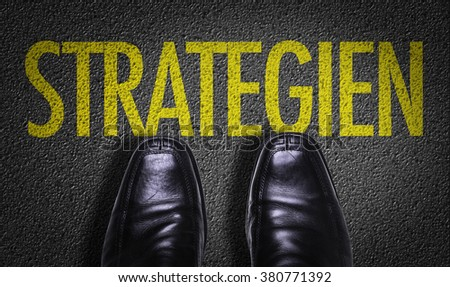 Top View of Business Shoes on the floor with the text: Strategy (in German) - stock photo