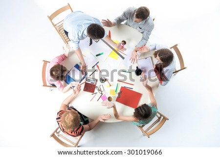 Top view of business team, sitting at a round table on white background. concept of finding a solution, bewilderment and surprise - stock photo