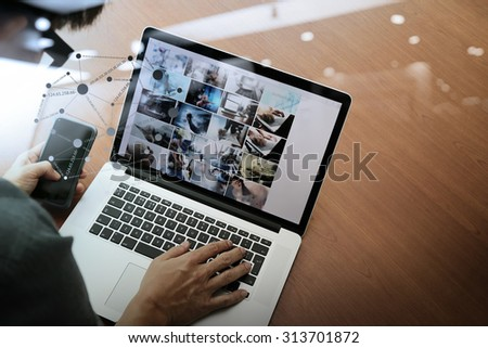 top view of businessman hand working with new modern computer and smart phone and business strategy on wooden desk with social media network as concept - stock photo