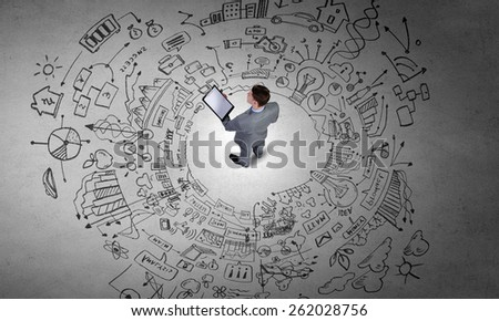 Top view of businessman looking at business sketches on floor