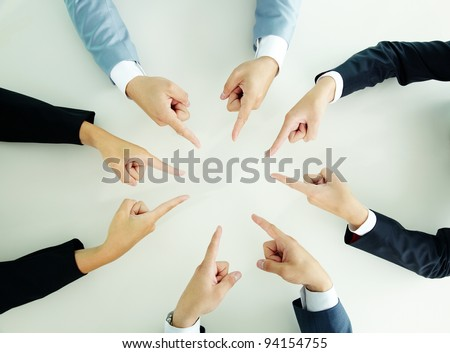 Top view of businesspeople pointing at each other - stock photo
