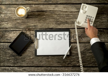 Top view of businessperson making a call with his office phone with digital tablet and blank piece of paper on a rustic wooden desk. Concept of telemarketing, feedback and customer support. - stock photo