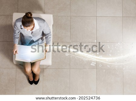 Top view of businesswoman sitting in chair and reading book