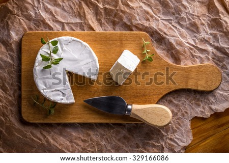 Top view of camembert cheese on cutting board - stock photo