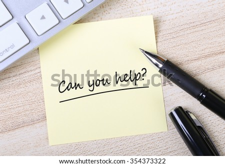 Top view of Can You Help sticky note pasted on the wooden desk with keyboard and pen aside. - stock photo