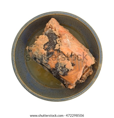 Top view of canned Pacific pink salmon in an old stoneware bowl isolated on a white background.