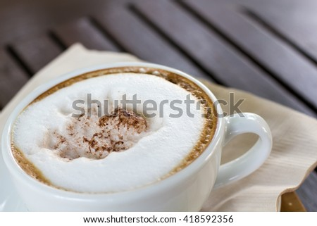 Top view of cappuccino coffee , in white cup.