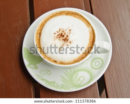 Top view of Capuchino coffee in a white cup on wooden background. - stock photo