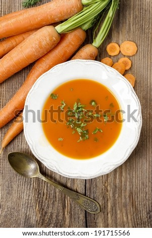 Top view of carrot soup on wooden table  - stock photo