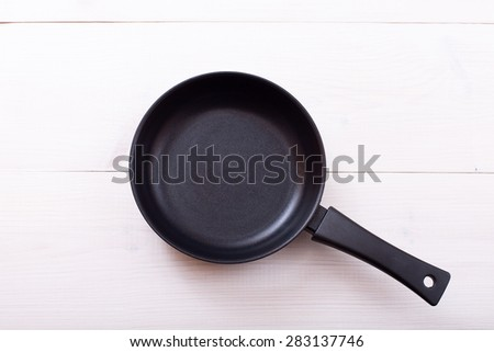 Top view of cast Iron empty pan on wooden background. Flat mock up for design. - stock photo