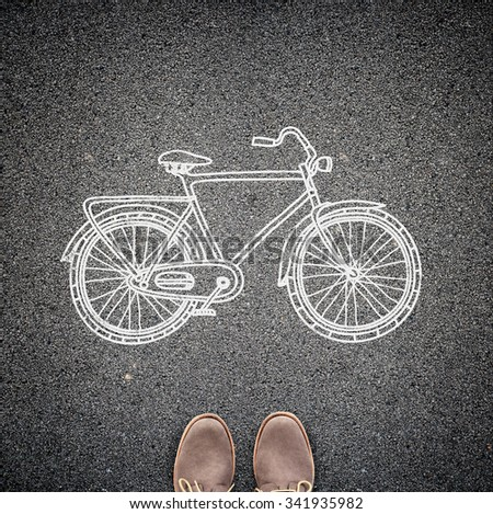 Top view of casual man's shoes and a sketched model of a bicycle on asphalt. A concept of environmental friendly way of travelling in the city. - stock photo