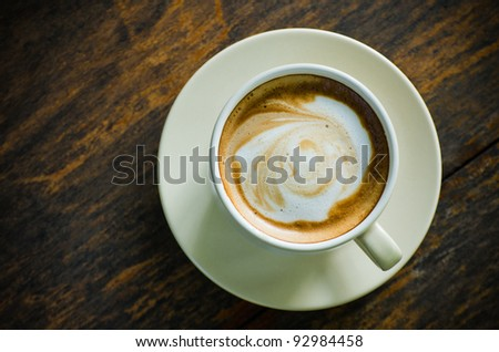 Top view of ceramic cup of coffee on wood table - stock photo
