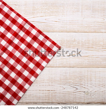 Top view of checkered napkin on white wooden table. Unique perspectives - stock photo