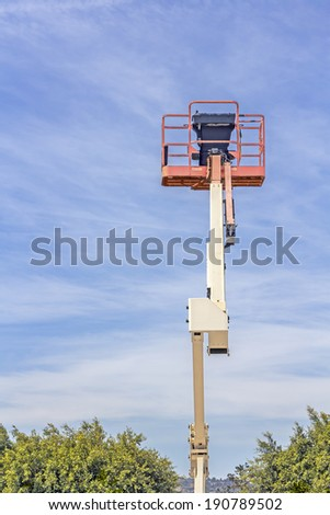 Top view of cherry picker or boom lift basket. Red, orange elevated work bucket platform, articulating bending arm. Trees, blue sky and clouds background.  Vertical composition.  - stock photo