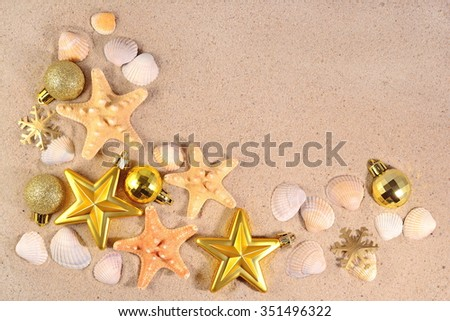 Top view of Christmas decorations, seashells and starfish on a beach sand