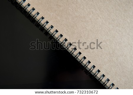 Top view of closed spiral blank recycled paper cover notebook on tablet screen background. close up shot