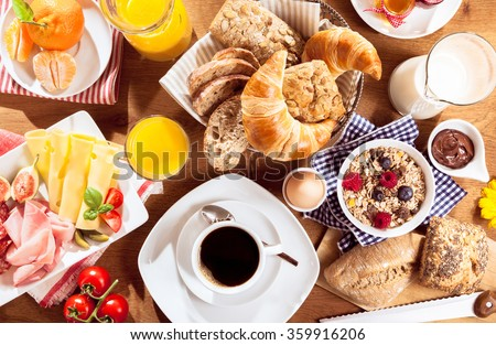 Top view of coffee, juice, fruit, bread and meat on table - stock photo