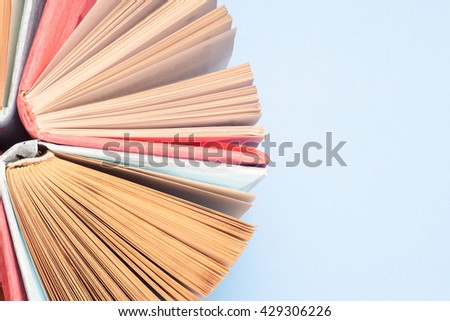 Top view of colorful hardback books in a circle. Open book, fanned pages,  free copy space. Back to school copy space. Education background. - stock photo