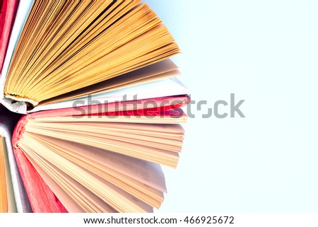 Top view of colorful hardback books in a circle. Open book, fanned pages,  free copy space. Back to school copy space. Education background.