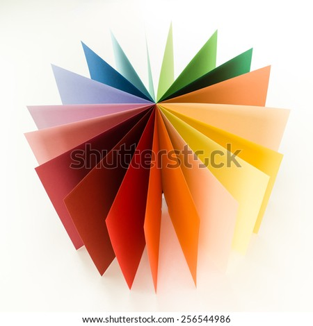 top view of colorful origami paper arranged in circle fan shape on white background - stock photo
