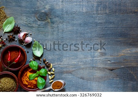 Top view of colorful  spices and herbs over dark old wood. Food and cuisine ingredients. Background with space for text. - stock photo