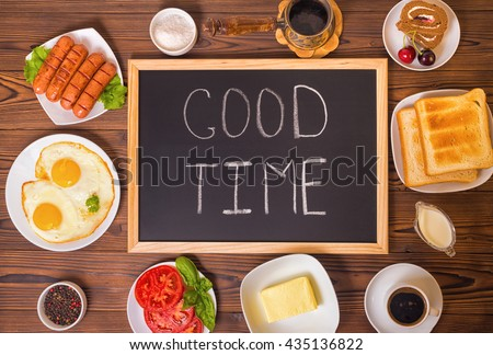top view of concept breakfast with handwritten text good time on blackboard with setting food products over wooden background  - stock photo