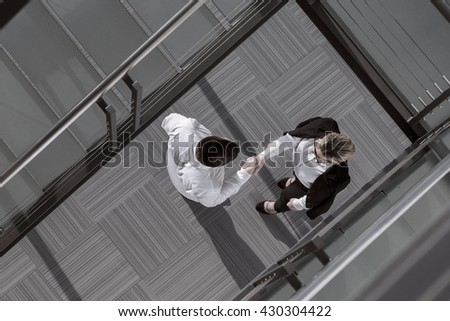 Top view of confident businessman and woman shaking hands in an office building lobby - stock photo