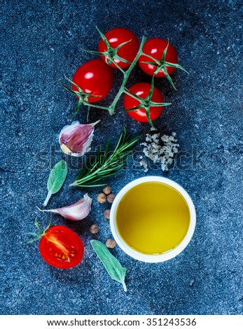 Top view of cooking ingredients (olive oil, peppercorns, tomatoes, garlic cloves, rosemary) on dark slate background. Fresh organic vegetables. Cooking, Healthy Eating or Vegetarian concept. - stock photo