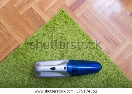 Top view of cordless handheld vacuum cleaner on green fluffy carpet on the parquet - stock photo