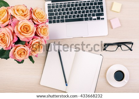 Top view of creative  woman's desktop with open notepad, pencil, glasses, coffee cup, roses and laptop keyboard