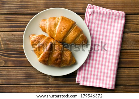 top view of croissants on plate and checkered napkin - stock photo