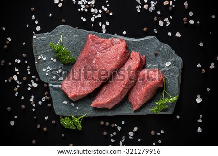 Top view of crude beef meat on stone surface - stock photo