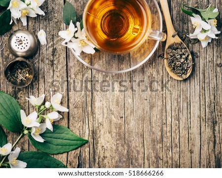 Top view of cup of asian hot green tea and jasmine flower on rustic wooden table with copyspace.