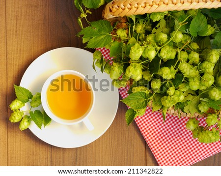 Top view of cup of hop tea, basket filled with hope blossom, wooden plank, - stock photo