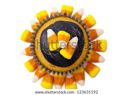 Top view of Cupcake with chocolate cream and candy corn displayed on white background. - stock photo