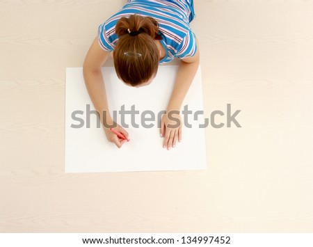 Top view of cute young woman while lying on floor and drawing.