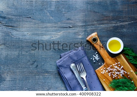 Top view of dark food background with wooden cutting board and ingredients on vintage kitchen table, place for text. - stock photo